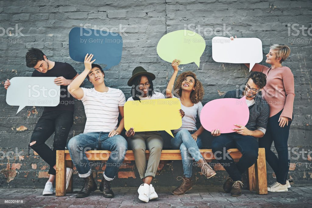 If you want to say something, say it here Shot of a diverse group of people holding up speech bubbles outside 20-29 Years Stock Photo