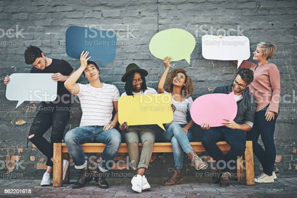 Shot of a diverse group of people holding up speech bubbles outside