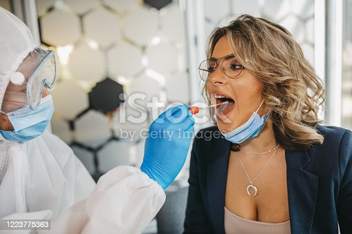 Young male doctor in protective suit taking swab test from young female patient