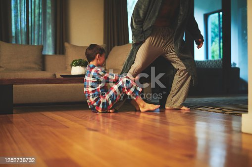 Shot of a little boy grabbing his father's leg as he tries to walk at home
