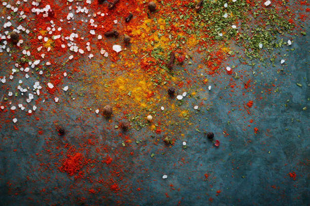 Вifferent spices scattered on the table, red paprika powder, turmeric, salt, cloves, pepper stock photo