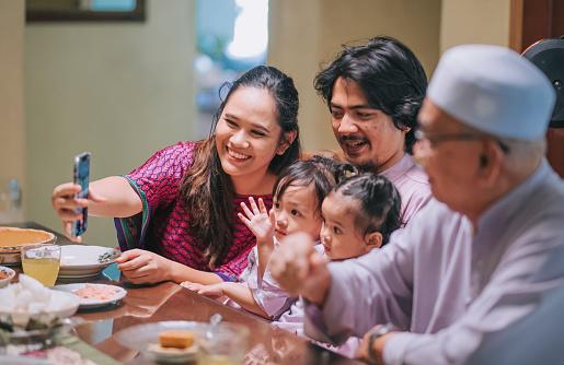 ramadan hari raya malaysian muslim multi generation family videocall relative enjoying dinner at home in dining room