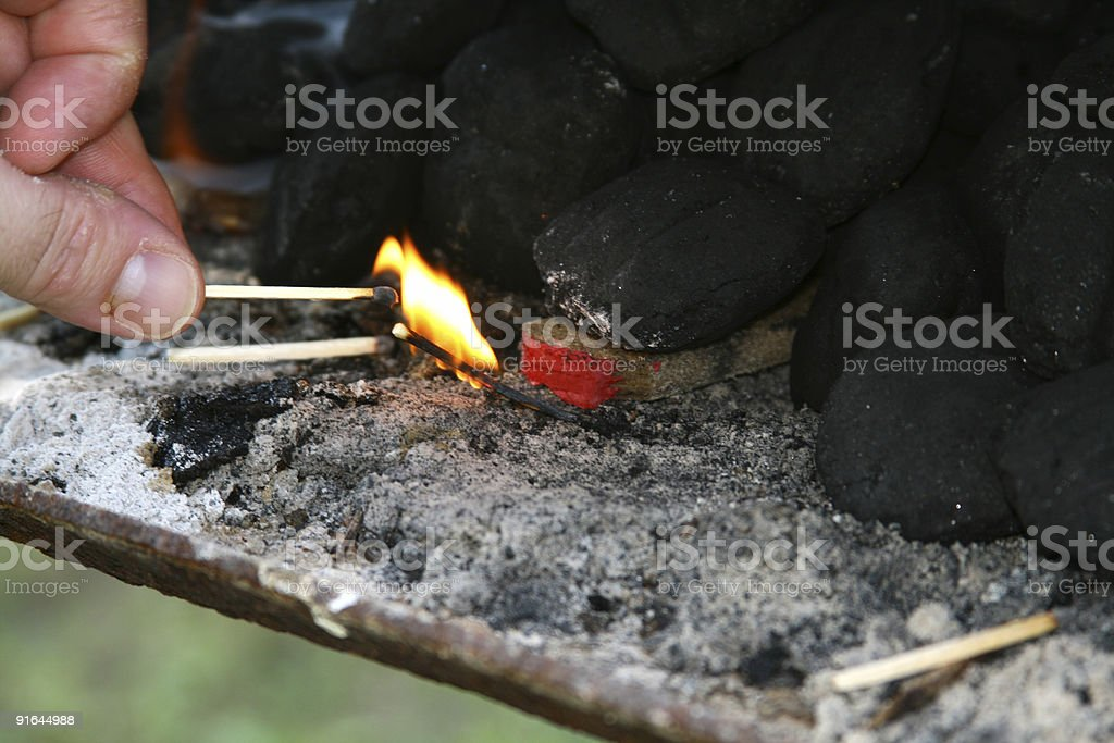 Ignighting: Hand Holding Match Lighting Charcoal Grill stock photo