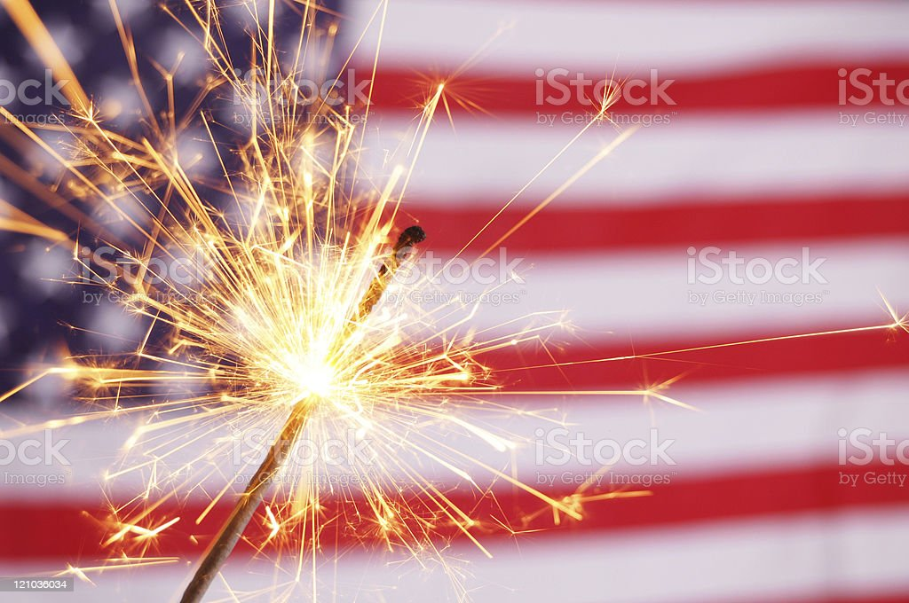 Ignited sparkler with the American flag in the background  stock photo