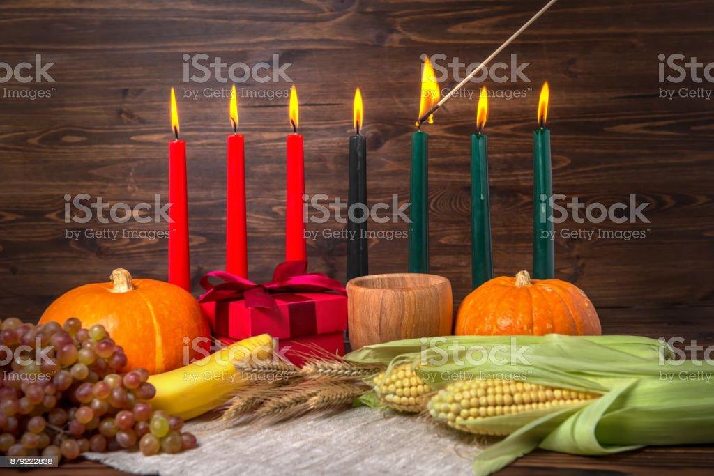 encendido de las velas tradicionales de Kwanzaa, concepto festival con caja de regalo, calabazas, orejas de trigo, uvas, maíz, plátano, tazón de fuente y frutas sobre fondo de madera, de cerca - foto de stock