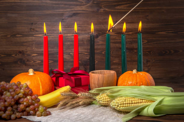 ignition of kwanzaa traditional candles, festival concept with gift box, pumpkins, ears of wheat, grapes, corns, banana, bowl and fruits on wooden background, close up - kwanzaa stock pictures, royalty-free photos & images