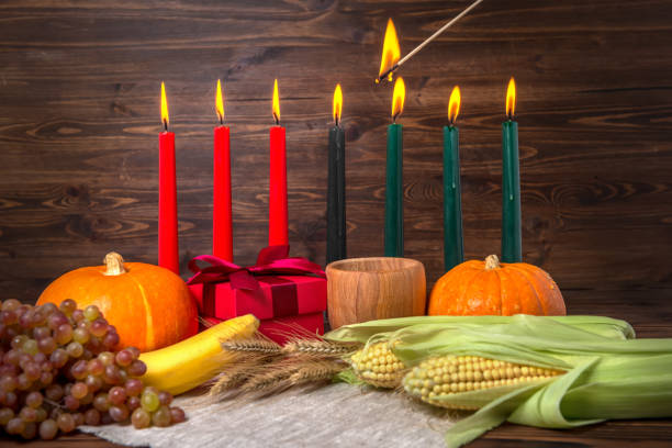 ignition of kwanzaa traditional candles, holiday concept with gift box, pumpkins, ears of wheat, grapes, corns, banana, bowl and fruits on wooden background, close up - kwanzaa stock pictures, royalty-free photos & images