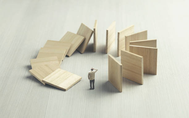 ignorant man watching domino collapsing on him, surreal concept stock photo