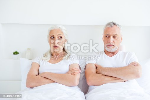 istock Ignore, sex, life concept. Sad, discomfort, angry, misunderstanding two people with gray hair lying in the bed look at each other in bright white interior with arms crossed over chests 1049802282