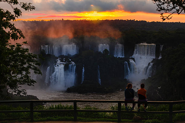 Iguacu, Brazil: Silhouette Of Tourists At The Famous Falls, Watching A Dramatic Sunset Over The Falls Near The Devil's Throat stock photo