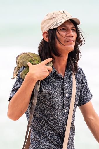 Koh Samui, Thailand - January 9, 2011: Thai man offers iguana for a photo to the tourists on the Chaweng beach of the Samui Island