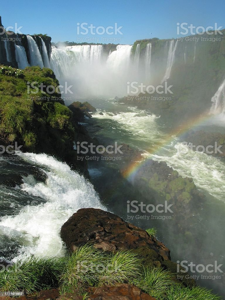 Iguazu Falls in Argentina with a rainbow and grassy hills royalty-free stock photo