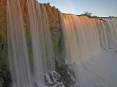 Impressive Iguacu falls with rainbow on the Argentina side of the border, one of the most beautiful waterfalls in the world and one of the seven Wonders of Nature, dramatic beauty in nature landscape - Idyllic Devil's Throat - international border of Brazilian Foz do Iguacu city, Parana State, Argentina Puerto Iguazu city, Misiones province and Paraguay - rainforest landscape panorama, South America