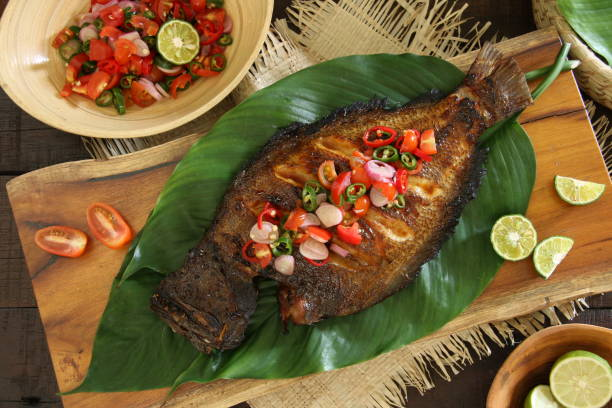Ikan Bakar Dabu-Dabu, the Grilled Fish with Fresh and Spicy Tomato Salsa from Manado, on Broad Green Leaves Ikan Bakar Dabu-Dabu, the popular grilled fish dish from Manado, North Sulawesi. The fish is lightly seasoned then grilled; served with the spicy tomato salsa. The fish is plated on a wooden serving block lined with layers of broad green leaves. Accompanied with extra salsa and limes. manado stock pictures, royalty-free photos & images