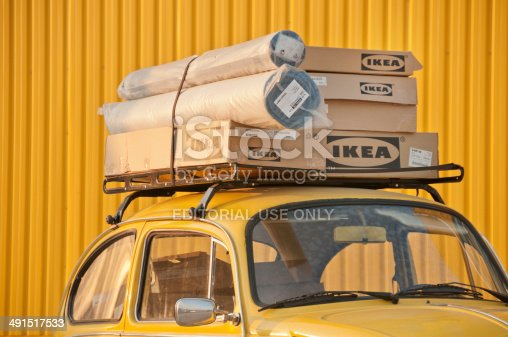 Izmir, Turkey - February 23, 2008: Group of boxes of furnitures installed at the top of an old fashioned VW car and bought from Ikea which is a Swedish company that designs and sells ready-to-assemble furniture (such as beds, chairs and desks), appliances and home accessories.  Image has been captured in front of Forum Bornova Ikea Market in Bornova, Izmir.