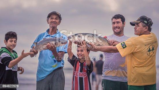 Ilha Do Mel, Paraná, Brazil - June 3, 2017: Native fishermen from Honey Island holding fish for the photo.