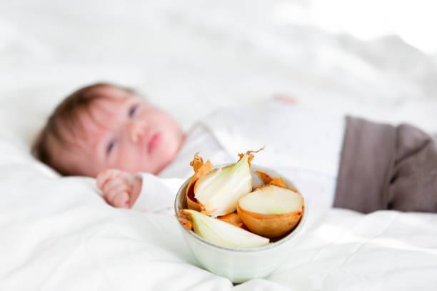 Kranke Baby wird mit ätherischen Ölen von Zwiebeln zu Hause im Bett behandelt. – Foto