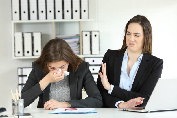 ill businesswoman and a colleague rejecting her - illness stock pictures, royalty-free photos & images