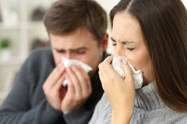 Ill couple coughing at home stock photo