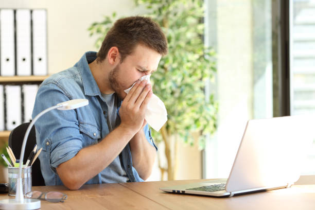 Ill entrepreneur sneezing at office Side view of an ill entrepreneur sneezing in a wipe at office near a window mucus stock pictures, royalty-free photos & images