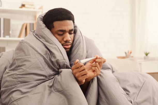 kranker mann bedeckt mit decke holding thermometer - erkältung und grippe stock-fotos und bilder