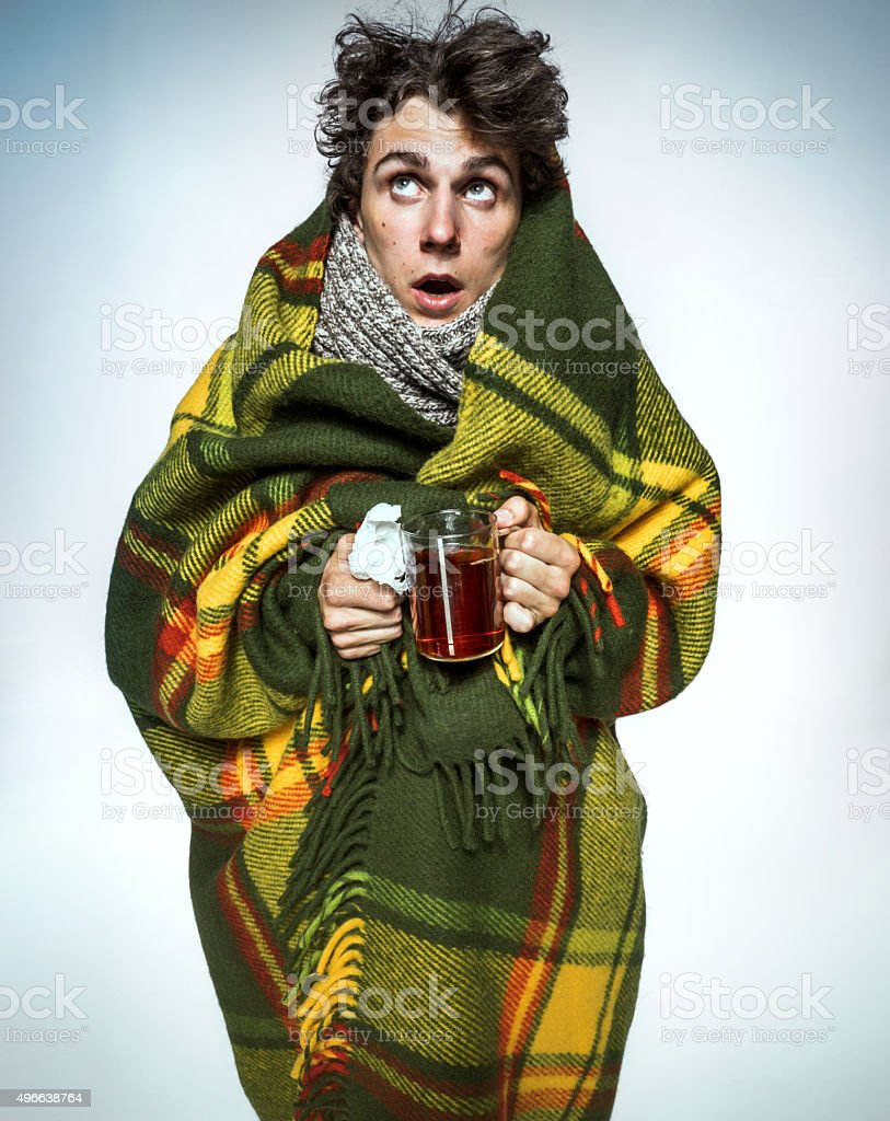 Ill Man covered with plaid blanket with hot tea stock photo