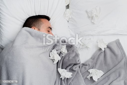 high angle view of an ill young caucasian man in bed, covered with a light gray blanket, surrounded by used tissues