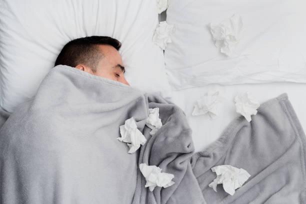 kranker mann im bett, umgeben von benutzt gewebe - erkältung und grippe stock-fotos und bilder