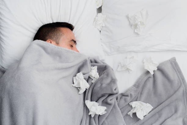 ill man in bed surrounded by used tissues high angle view of an ill young caucasian man in bed, covered with a light gray blanket, surrounded by used tissues flu stock pictures, royalty-free photos & images