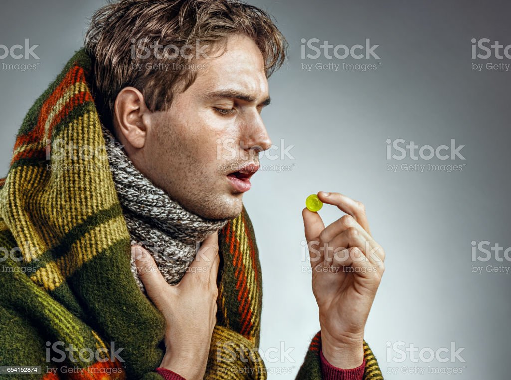 Ill man with open mouth take pills for throat. stock photo