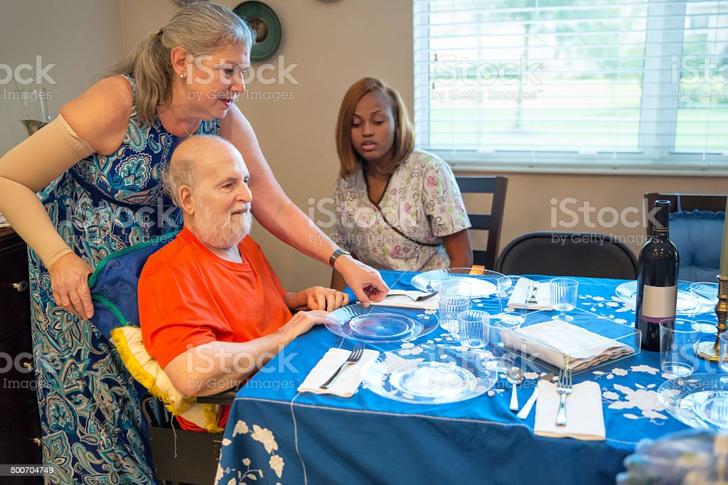 Ill man with wife and caregiver at Passover sedar. stock photo