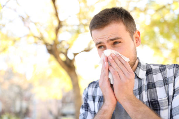 Ill or allergic man coughing in a park stock photo