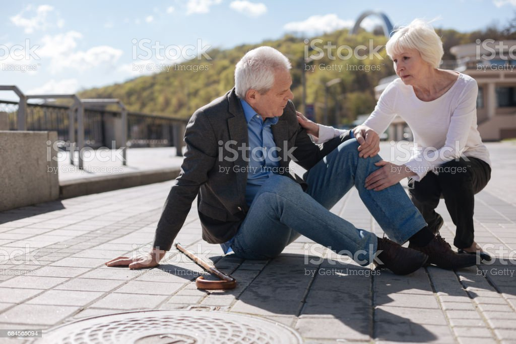 Ill pensioner having pain in his knee outdoors stock photo