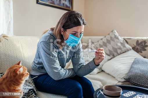 Ill infected woman checking thermometer having fever. Girl wearing protective mask while having cold, flu taking pills at home. Healthcare