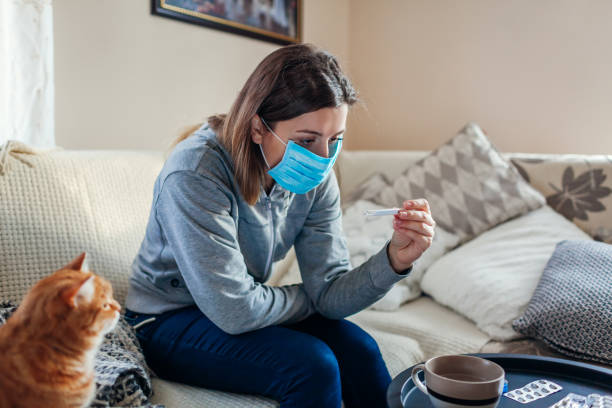mujer enferma revisando el termómetro con fiebre. chica usando máscara protectora mientras tiene resfriado, gripe en casa. atención sanitaria - enfermedad fotografías e imágenes de stock