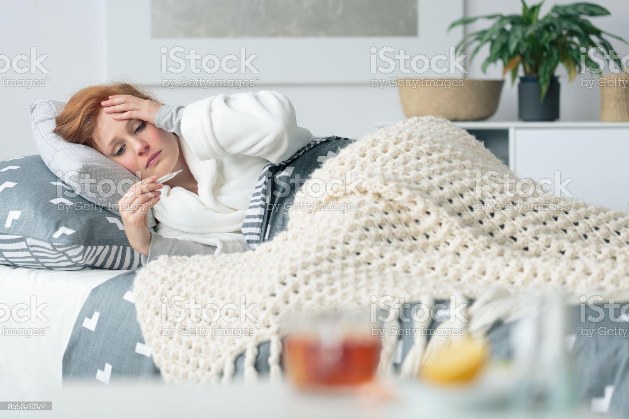 Ill woman looking at thermometer - Foto stock royalty-free di Influenza - Malattia infettiva