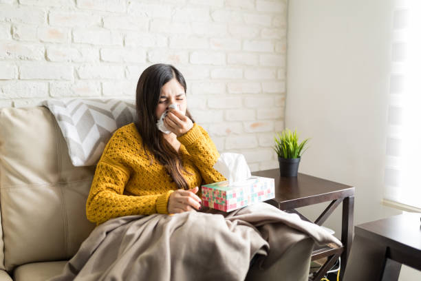 Ill Woman Sneezing At Home Sick woman blowing her nose in tissue while sitting on sofa at home mucus stock pictures, royalty-free photos & images