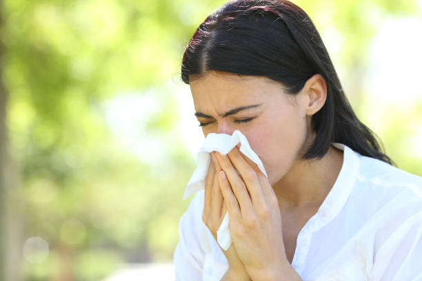 Ill woman sneezing covering mouth with a wipe in a park stock photo