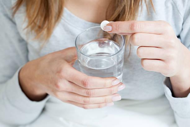 ill woman taking aspirin - aspirin stok fotoğraflar ve resimler
