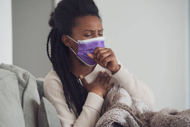 Ill woman with face mask coughing lying down and resting. stock photo