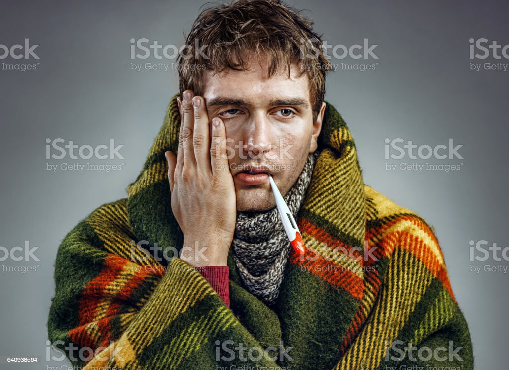 Ill young man with a thermometer in his mouth stock photo