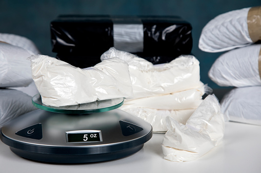 Confiscated illegal substance with measuring scale indicating 5 ounces, and a briefcase full of American currency.