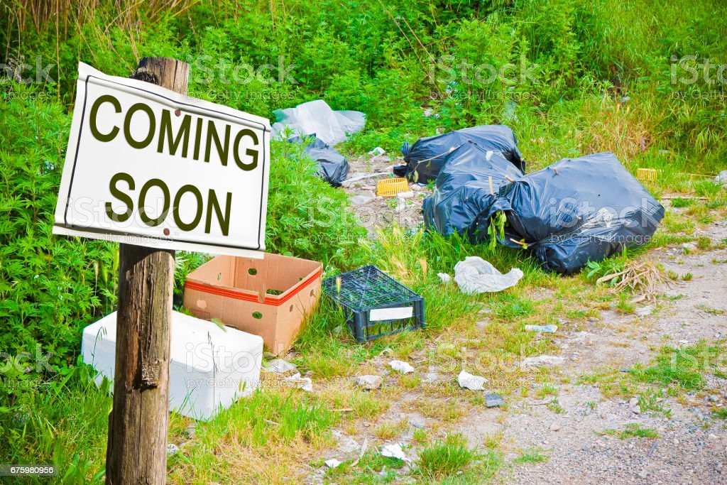 Illegal dumping abandoned in nature whit coming soon sign - concept image stock photo