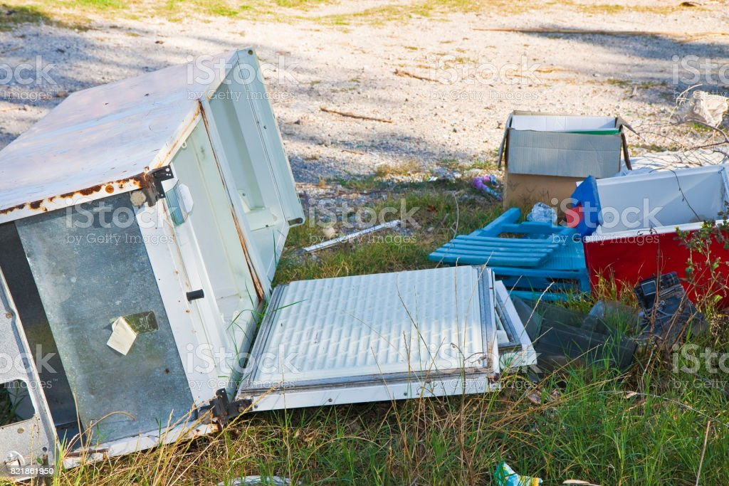 Illegal dumping with cardboard boxes, plastic bags and domestic appliances abandoned in nature stock photo