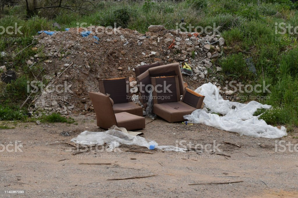 Old armchairs broken furniture and pile of debris rubble and trash by...