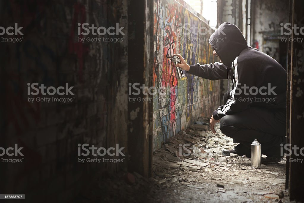 Illegal Young man Spraying black paint on a Graffiti wall. stock photo