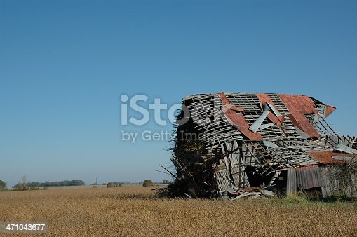 Rural barn on a family farm that has fallen into disrepair.  Equipment and straw bales have tumbled out of the barn.