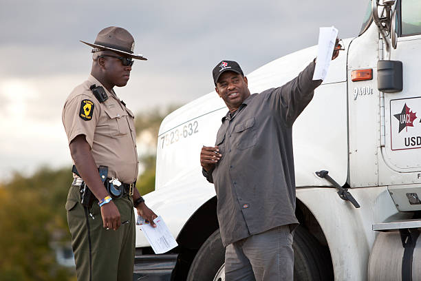 Illinois State Trooper Itasca, IL, USA - September 30, 2011: An unidentified Illinois State Police Trooper speaks to an unidentified truck driver on the side of the road in the Western Suburbs of Chicago, IL. trooper stock pictures, royalty-free photos & images