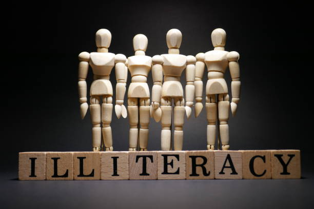 Illiteracy Wooden text cubes and wooden figurines - Illiteracy illiteracy stock pictures, royalty-free photos & images