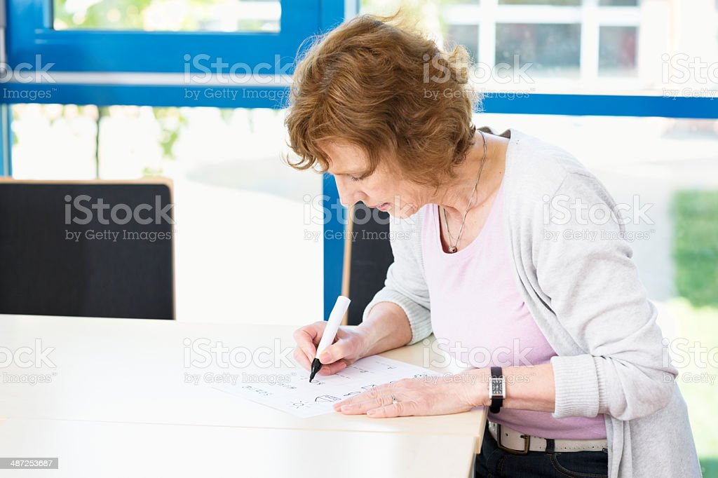 Illiterate woman learning to write stock photo